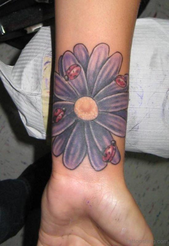 Purple Daisy Flower With Ladybugs Tattoo On Wrist