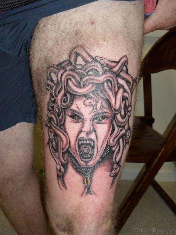 Black And Grey Horror Medusa Face Tattoo On Man Thigh