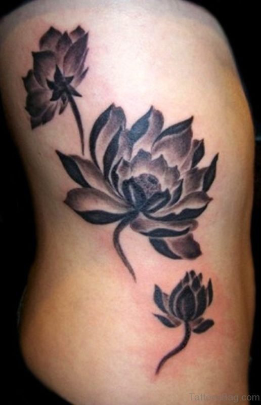 Black Ink Three Lotus Flowers Tattoo On Side Rib