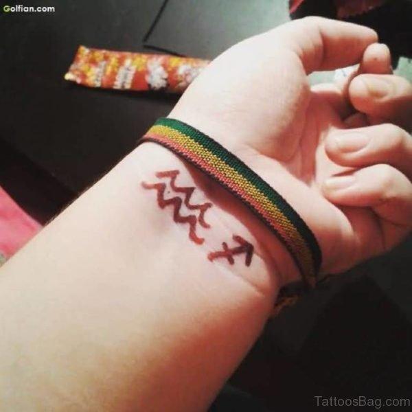 Brown Aquarius Tattoo On Wrist