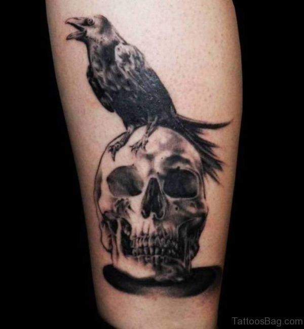 Crow Sitting On Skull Tattoo On Leg