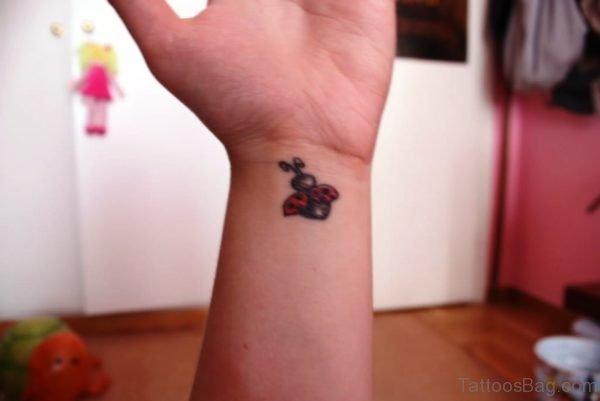 Cute Flying Ladybug Wrist Tattoo