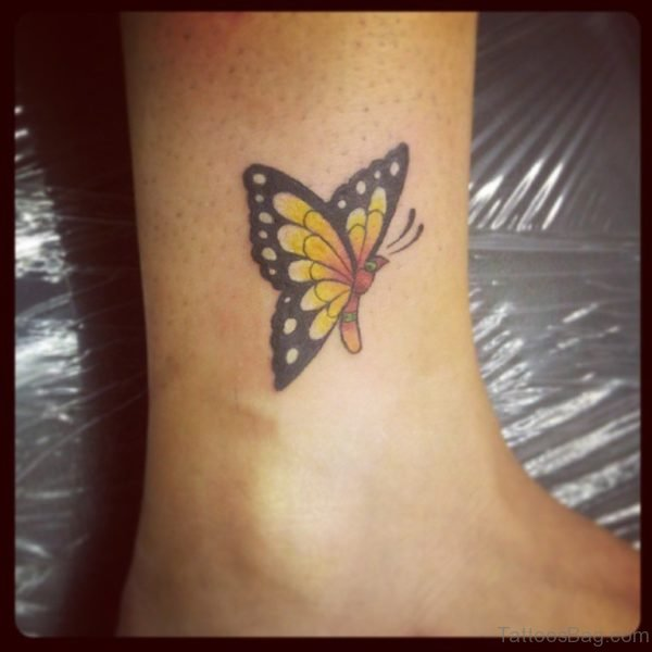 Cute Yellow Black Ink Butterfly Tattoo On Ankle