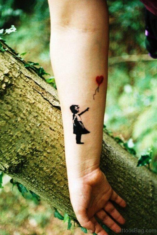Girl Catching Balloon Tattoo On Wrist