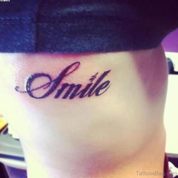 Glowing Smile Word Tattoo On Rib Side
