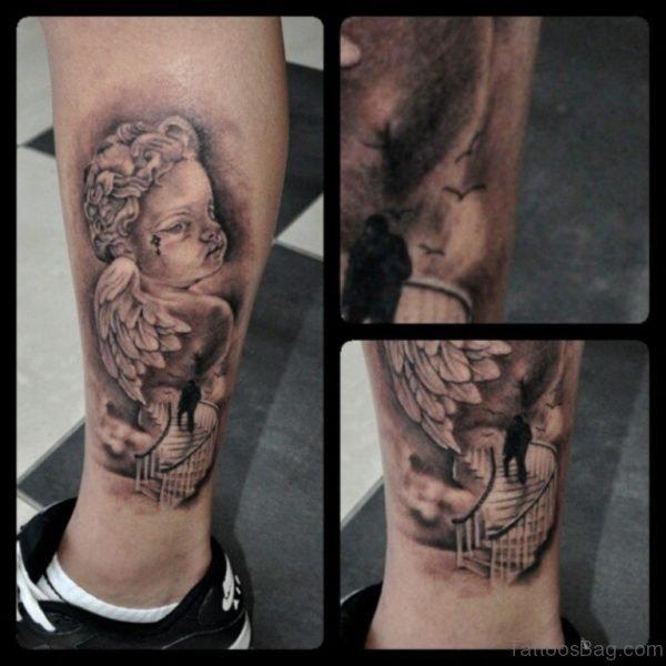 Grey Ink Cherub Angel Tattoo On Leg