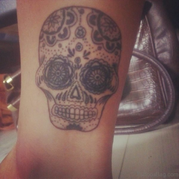 Grey Ink Suagr Skull Tattoo On Ankle