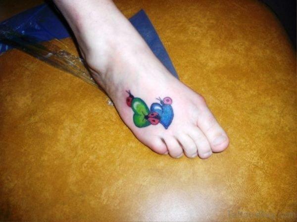 Ladybugs On Colorful Hearts Tattoo