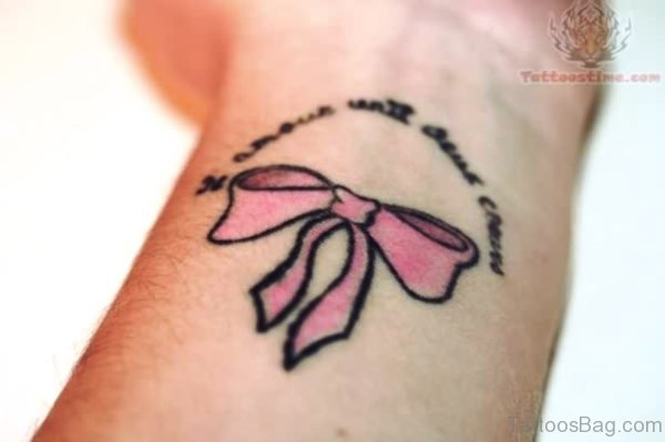 Light Pink Color Bow Tattoo On Wrist