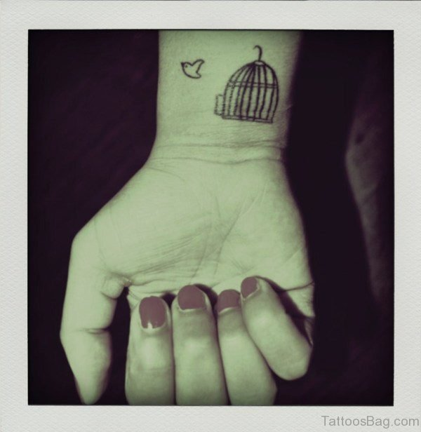 Nice Flying Bird And Cage Tattoo On Wrist