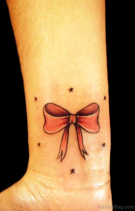 Red Ink Bow Tattoo On Wrist