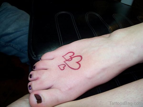 Red Ink Heart Tattoo On Foot