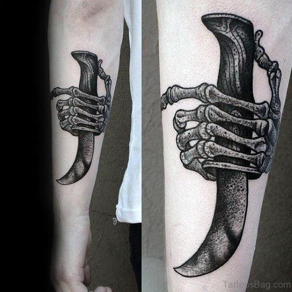 Skeleton Hand Dagger Tattoo On Arm