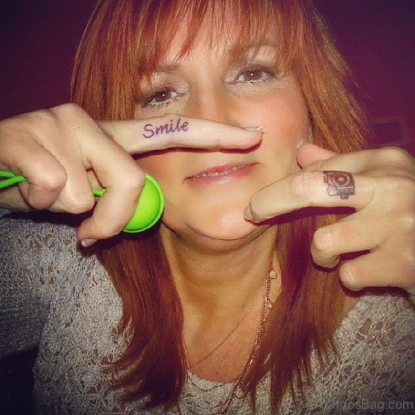Smile And Camera Tattoo On Finger