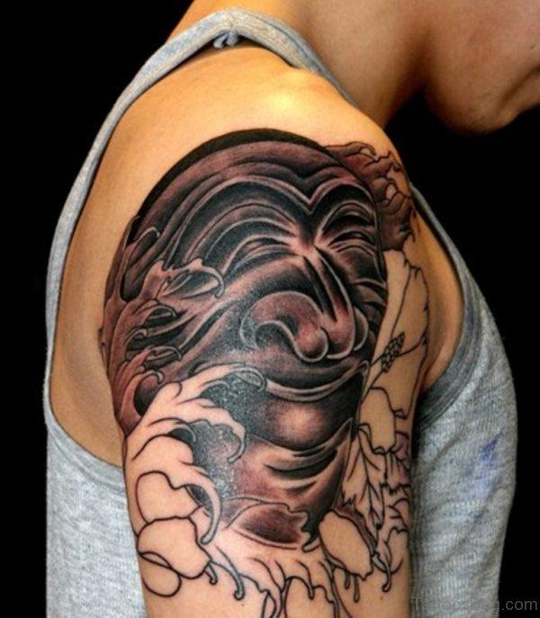 Black And Grey Korean Mask Tattoo On Shoulder