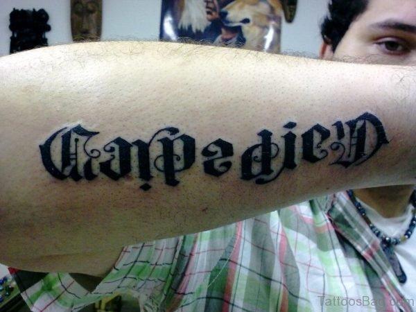Black Inked Carpe Diem Tattoo On Arm