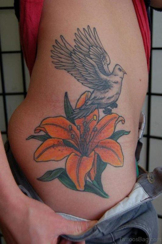 Flying Bird With Orange Lily Tattoo On Waist