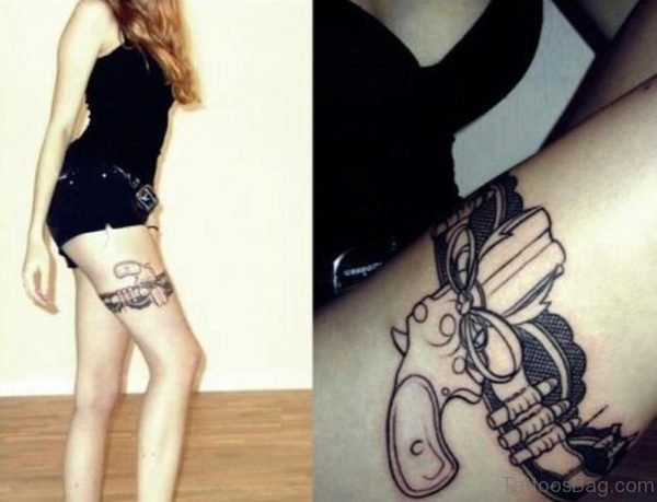 Girl With Gun Tattoo On Thigh