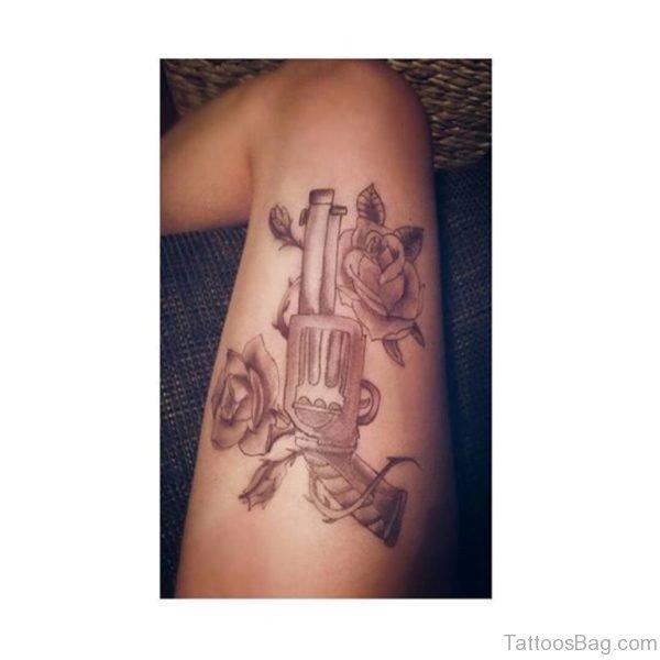 Nice Rose And Gun Tattoo