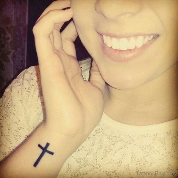 Smiling Girl With Black Cross Wrist Tattoo