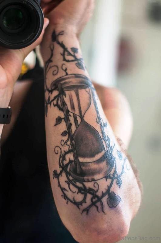 Vine And Sandclock Tattoo On Arm